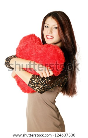Young beautiful woman holding a heart-shaped pillow - stock photo
