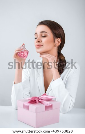 young beautiful woman holding a spray bottle of perfume and smelling aroma, a gift on the table - stock photo