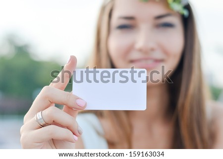 Young beautiful woman holding blank business card with copy space happy smiling & looking at camera - stock photo