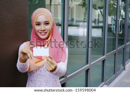Young beautiful woman holding  blank card and smiling