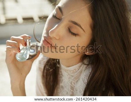young beautiful woman holding bottle of perfume and smelling aroma. horizontal shot - stock photo
