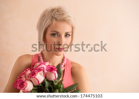 Young beautiful woman holding bouquet of pink roses. She is very satisfied. Valentine's day or international women's day celebration.