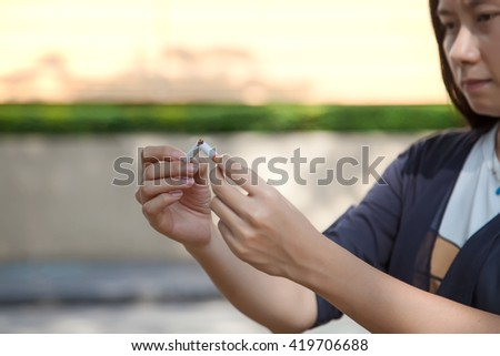 """Young beautiful woman holding broken cigarette, people smoke cigarette look like trying to commit suicide, In the day """" World No Tobacco Day"""" please quit or stop smoke for good health. - stock photo"""