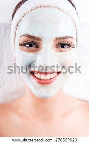 Young beautiful woman holding mask on the face in a spa salon.