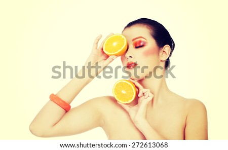 Young beautiful woman holding orange - stock photo