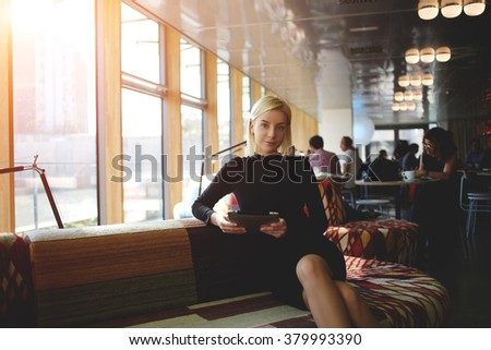 Young beautiful woman holding touch pad in hands while waiting for business lunch in modern coffee shop interior, female entrepreneur posing with digital tablet while sitting in comfortable restaurant - stock photo