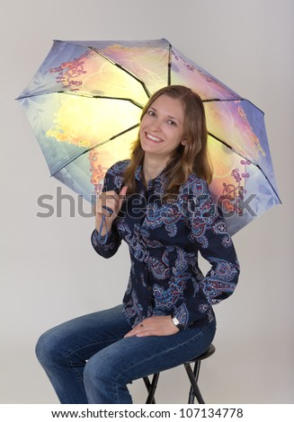 Young beautiful woman holding umbrella, on grey background