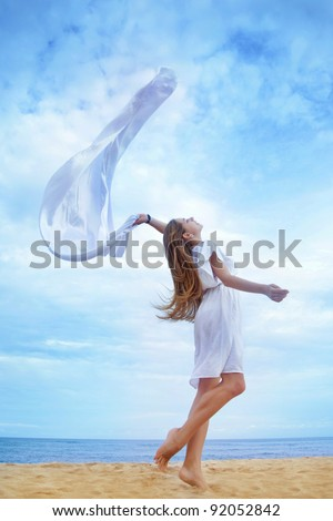 Young beautiful woman holding white flag near ocean, Indonesia, Bali