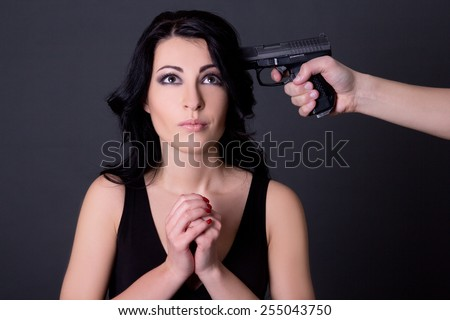 young beautiful woman hostage and male hand with gun over grey background - stock photo