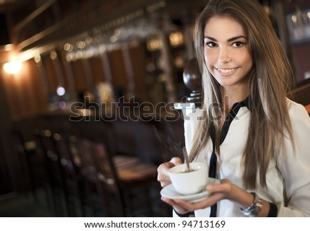 young beautiful woman in a cafe with a cup of coffee - stock photo