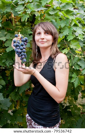young beautiful woman in a garden with the cluster of vine