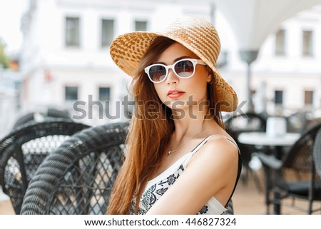 Young beautiful woman in a hat and sunglasses relaxing in the restaurant.