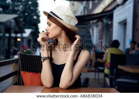 Young beautiful woman in a hat in a cafe on a summer street.