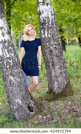 young beautiful woman in a hat standing at the birch