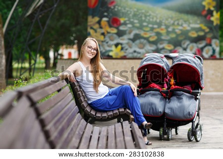 Young beautiful woman in a park with a double jogging stroller with two kids, her identical twin daughters