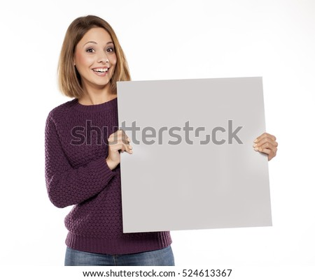 young beautiful woman in a purple sweater and jeans, holding a blank board for advertising