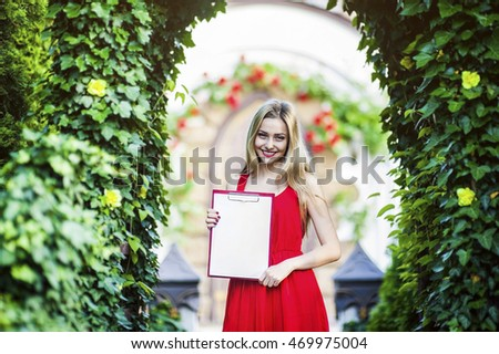 Young beautiful woman in a red dress holding a folder and standing under the arch with flowers.