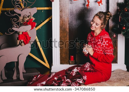 Young beautiful woman in a red warm pajamas with scandinavian ornaments sitting near decorative fireplace and drinking hot tea or cocoa. Christmas mood - stock photo