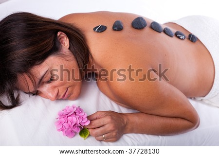 young beautiful woman in a spa enjoying a hot stone treatment