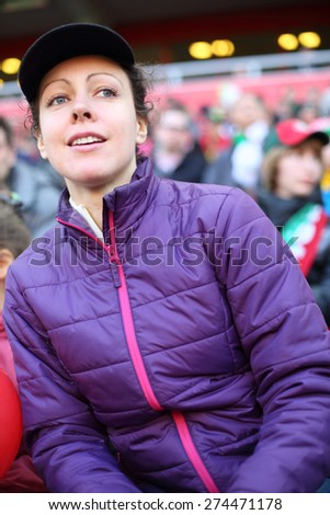 Young beautiful woman in a sports jacket and a cap at stadium - stock photo
