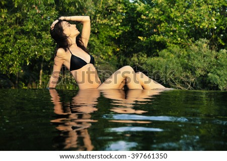 Young beautiful woman in a swim suit sitting on the edge of the pond near a waterfall - stock photo