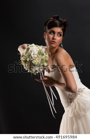 Young beautiful woman in a wedding dress on a black studio background