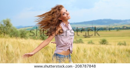 Young, beautiful woman in a wheat field. Tuscany, Italy  - stock photo