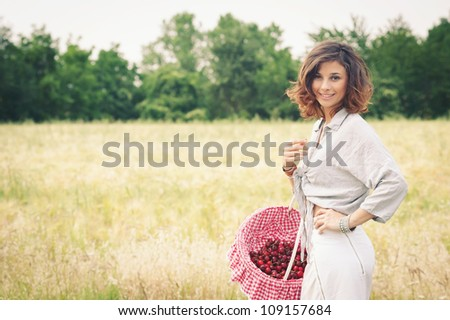 Young beautiful woman in a wheat field with cherries basket. - stock photo