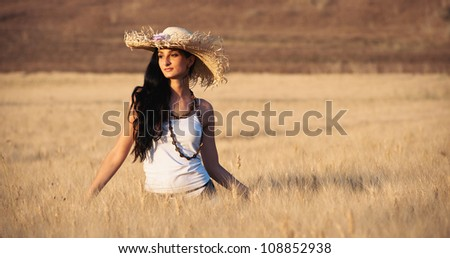 Young beautiful woman in a wheat field with white dress and straw hat. - stock photo