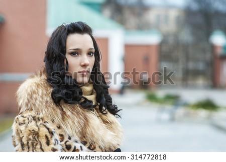 Young beautiful woman in an orange fur coat looks upwards. - stock photo
