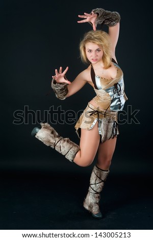 Young beautiful woman in barbarian costume at black background