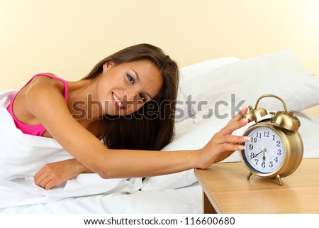 young beautiful woman in bed and alarm clock - stock photo