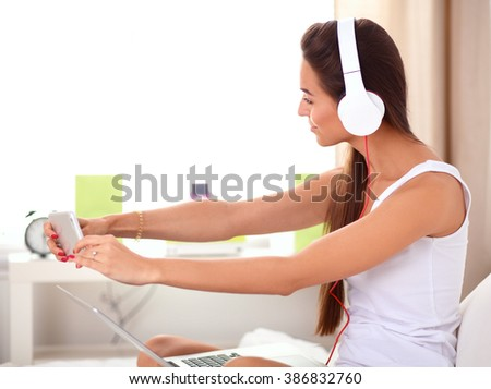 Young beautiful woman in bed listening to music