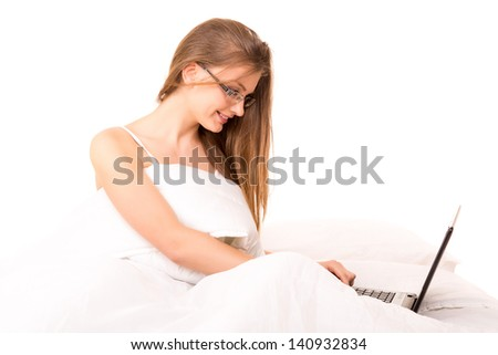 Young beautiful woman in bed, working or relaxing with her computer