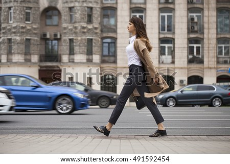 Young beautiful woman in beige coat with a bag walking on the autumn street