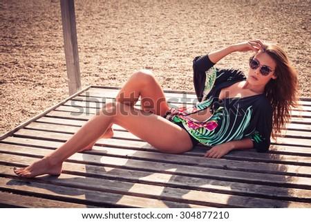 young beautiful woman in bikini and summer top pose on the lake beach, full body shot - stock photo