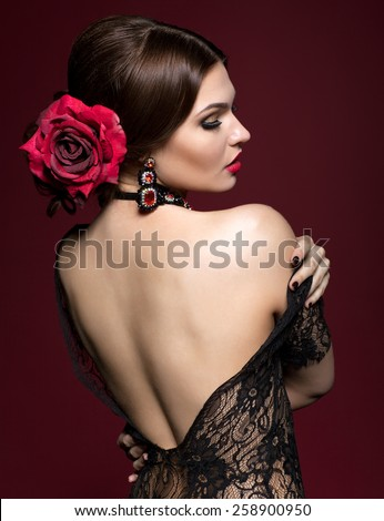 Young beautiful woman in black dres and black rose flower in hair from back side on dark marsala color background - stock photo
