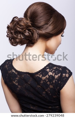 Young beautiful woman in black dress from back side on gray background  - stock photo