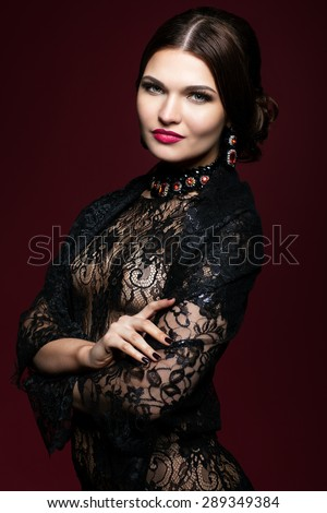 Young beautiful woman in black dress on dark red marsala color background - stock photo
