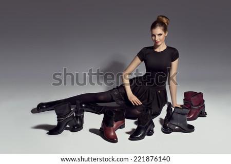 young beautiful woman in black dress posing with shoes - stock photo