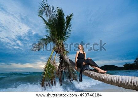 Young beautiful woman in black dress, sitting on the palm tree above sea on sunset time. Tropical vacation.