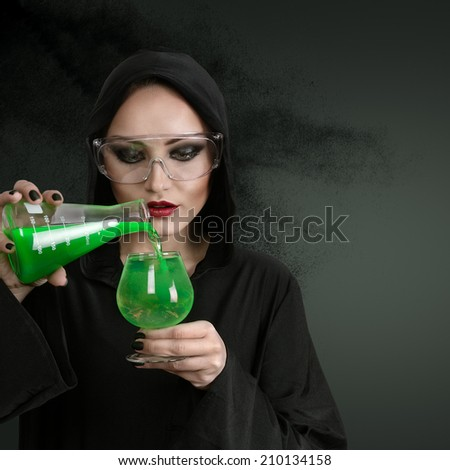 Young beautiful woman in black hood with poison - stock photo