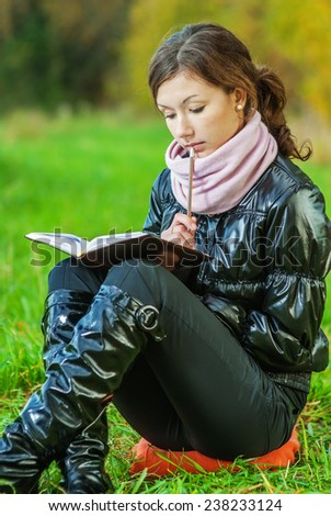 Young beautiful woman in black jacket reads book against autumn nature.
