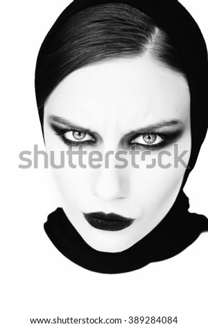 Young beautiful woman in black with gothic fashion makeup , posing on white background. Halloween.