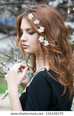 Young beautiful woman in  blooming garden - stock photo