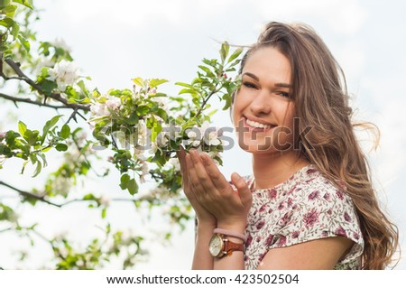 Young beautiful woman in blooming garden enjoying freetime and relaxing in the nature