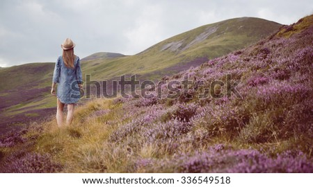 young beautiful woman  in blue dress  the heather meadows in Scotland watching the mountains.  - stock photo