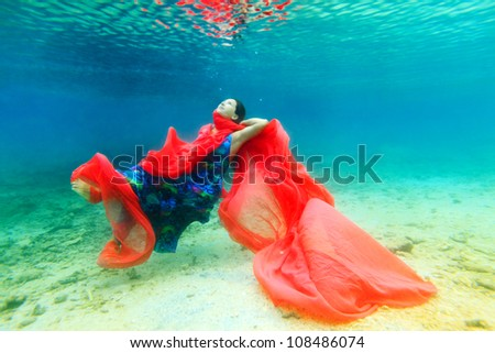 Young beautiful woman in blue dress underwater - stock photo