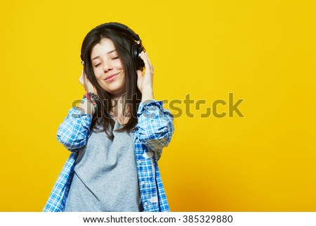 Young beautiful woman in bright outfit enjoying the music over yellow wall with copy space. Studio portrait of a girl with eyes closed wearing headphones - stock photo