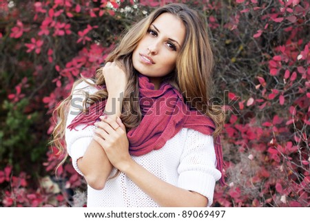 Young beautiful woman in colorful autumn leaves